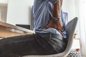 Businessman working sitting at desk feels unhealthy suffers from lower back pain. Damage of intervertebral discs, spinal joints, compression of nerve roots caused by wrong posture and sedentary work.